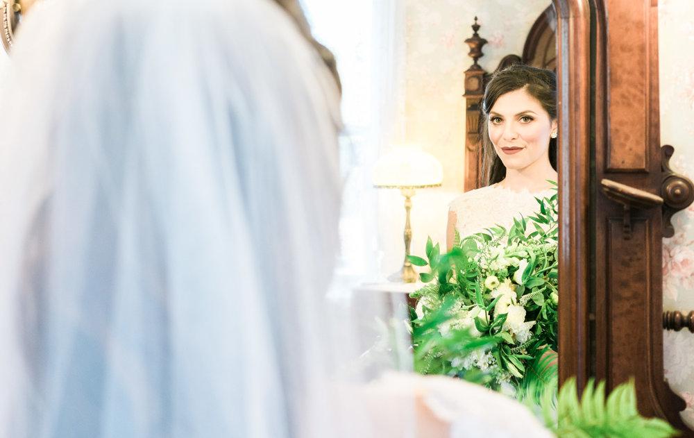 bride-looking-in-the-mirror-bridesmaid-helping-bride-get-ready-elliston-vineyard-wedding-photographer-afewgood-clicks.net