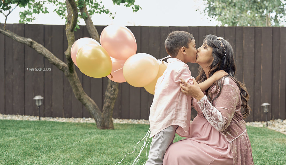 Toddler-kissing-his-mom-during-the-maternity-shoot